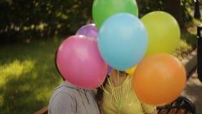 Paar die rond in het park met ballons voor de gek houden stock video