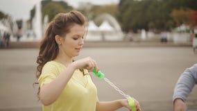 Paar die rond in het park met zeepbels voor de gek houden stock footage