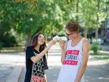 Paar die roomijs in een park eten Vriend en meisje op een vage natuurlijke achtergrond Het dateren van concept De ruimte van het  Royalty-vrije Stock Afbeelding