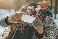 Paar die selfie in de winterbos maken Stock Afbeeldingen