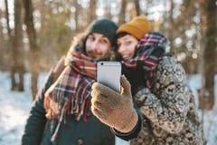 Paar die selfie in de winterbos maken Stock Foto's