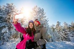 Paar die selfie en pret op de sneeuw hebben maken Stock Foto's