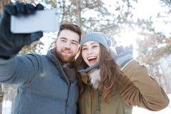 Paar die selfie foto in de winterpark maken Royalty-vrije Stock Afbeelding
