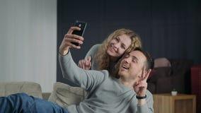Paar die selfie op smartphonecamera maken, en thuis possing glimlachen stock videobeelden