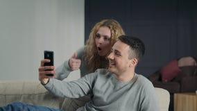 Paar die selfie op smartphonecamera maken, en thuis possing glimlachen stock video