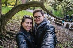 Paar die selfie in park onder de boom nemen stock afbeeldingen