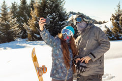 Paar die snowboarder zich op een bergbovenkant bij zonsondergang en maki bevinden Royalty-vrije Stock Fotografie