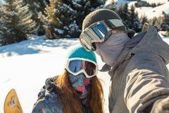 Paar die snowboarder zich op een bergbovenkant bij zonsondergang en maki bevinden Royalty-vrije Stock Afbeeldingen