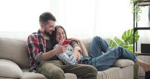 Paar die sociale media doorbladeren die mobiele telefoon op bank met behulp van stock footage