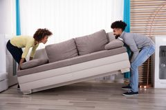 Paar die Sofa In Living Room opheffen royalty-vrije stock foto