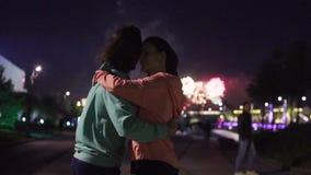 Paar die tegen vuurwerk in nachtstad dansen
