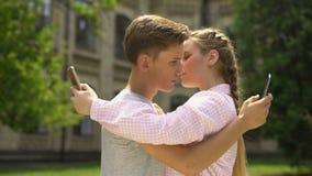 Paar die telefoon met behulp van terwijl het koesteren, verslaving aan sociaal netwerkenconcept stock footage