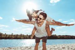 Paar die terwijl het doorbrengen van tijd aan strand op de zomerdag vervoeren per kangoeroewagen royalty-vrije stock foto