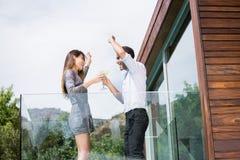 Paar die terwijl het drinken van cocktails in balkon dansen royalty-vrije stock fotografie