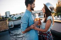 Paar die terwijl het hebben van een drank op dak terrasse flirten stock foto