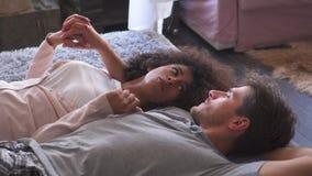 Paar die terwijl het ontspannen in bed spreken stock video