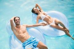 Paar die terwijl het ontspannen op opblaasbare ring glimlachen royalty-vrije stock foto