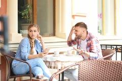 Paar die terwijl het zitten in koffie, in openlucht debatteren Problemen in verhouding stock fotografie