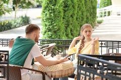 Paar die terwijl het zitten in koffie, in openlucht debatteren Problemen in verhouding stock afbeeldingen