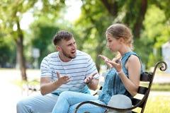Paar die terwijl het zitten op bank in park debatteren Problemen in verhouding royalty-vrije stock afbeeldingen