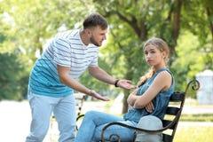 Paar die terwijl het zitten op bank in park debatteren Problemen in verhouding stock afbeelding