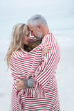 Paar die terwijl verpakt in een strandhanddoek omhelzen Stock Foto
