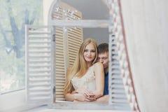 Paar die thuis in de spiegel dichtbij het venster kijken Mooie houdende van familie Kerel en meisje die samen knuffelen De dag va royalty-vrije stock foto's
