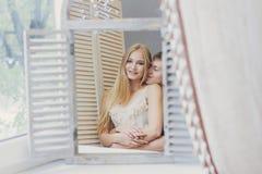 Paar die thuis in de spiegel dichtbij het venster kijken Mooie houdende van familie Kerel en meisje die samen knuffelen De dag va royalty-vrije stock afbeeldingen