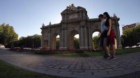 Paar die Triomfantelijke boog Puerta DE Alcala Madrid lopen stock videobeelden