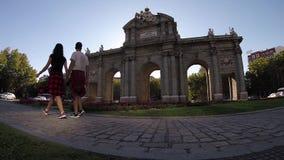 Paar die Triomfantelijke boogpuerta DE Alcala Madrid Langzame Motie lopen stock footage