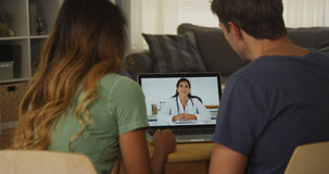 Paar die tussen verschillende rassen met arts op laptop spreken stock foto