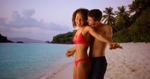 Paar die tussen verschillende rassen zich op Caraïbische kust bevinden die bij horizon staren Royalty-vrije Stock Foto