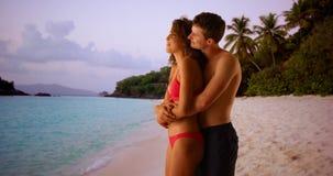 Paar die tussen verschillende rassen zich op Caraïbische kust bevinden die bij horizon staren Stock Fotografie