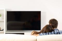 Paar die TV-het scherm op mening letten Stock Foto