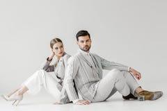 paar die van aantrekkelijke modellen in uitstekende kleren op vloer zitten en rijtjes leunen royalty-vrije stock fotografie