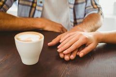 Paar die van de handen van een koffieholding genieten Royalty-vrije Stock Afbeeldingen