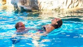 Paar die van in de pool genieten een mooie en ontspannen dag stock foto's