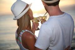 Paar die van dranken in zonsondergang genieten royalty-vrije stock fotografie