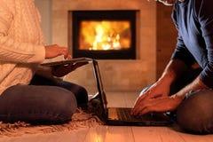 Paar die van freelancers bij de vloer met laptop en een tablet situeren stock foto
