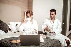 Paar die van freelancers hotelbadjassen dragen die koffie in bed drinken stock foto's