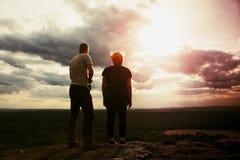 Paar die van prachtige ogenblikken genieten tijdens zonsondergang Jong paar wandelaars op de piek van rotshorloge over vallei aan royalty-vrije stock foto's