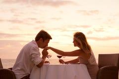 Paar die van romantisch sunnsetdiner op het strand genieten stock afbeelding