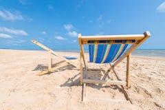 Paar die van stoelen op zandig strand op zonnige dag blu zoeken Royalty-vrije Stock Afbeelding
