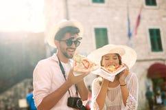Paar die van toerist pizza op straat eten royalty-vrije stock fotografie