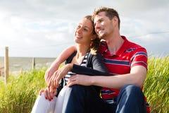 Paar die van vakantie in strandduin genieten Stock Afbeeldingen
