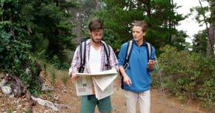 Paar die van wandelaar een kaart en een kompas kijken stock videobeelden
