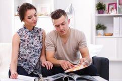 Paar die verfmonster voor nieuw huis kiezen, die bij het bureau werken Royalty-vrije Stock Afbeelding