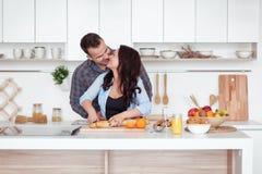 Paar die vers organisch sap in keuken samen maken Een jonge vrouw in een blauw overhemd snijdt een baguette Een mens koestert Royalty-vrije Stock Afbeelding