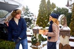 Paar die vers verminderde Kerstboom en giftdozen leegmaken uit autoboomstam om huis te verfraaien Gelukkige man en vrouw stock foto