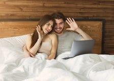 Paar die videogesprek op laptop in bed maken stock foto